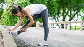 Sportkvinna som sträcker att köra i gataPark City stads- bakgrund Royaltyfri Bild