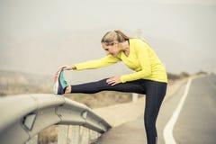 Sportkvinna som sträcker benmuskeln efter rinnande genomkörare på asfaltvägen med torrt ökenlandskap i hård konditionutbildningsp royaltyfria foton