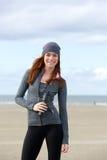 Sportkvinna som utomhus ler med vattenflaskan Arkivfoton