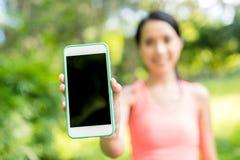Sportkvinna som visar den tomma skärmen av mobiltelefonen royaltyfri bild