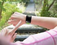 Sportkvinnafingret som pekar exponeringsglas för smartwatchmellanrumssvart, böjde till Arkivfoton