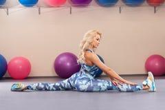 Sportkvinnan sitter på en tvinna Idrotts- flicka som gör sträcka övning i konditionrummet aktiv livsstil royaltyfri bild