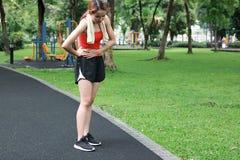 Sportkvinnan som har magen, sm?rtar under ink?rt parkera royaltyfri fotografi