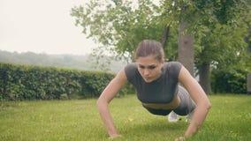 Sportkvinnan som utbildning skjuter, ups övning på gräs i sommar parkerar stock video