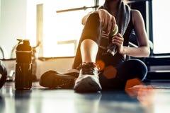 Sportkvinnasammanträde och vila efter genomkörare eller övning i passform royaltyfria foton