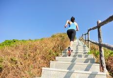 Sportkvinnaspring på bergtrappa Arkivbild