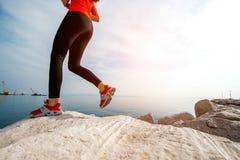 Sportkvinnaspring på den steniga stranden royaltyfri bild