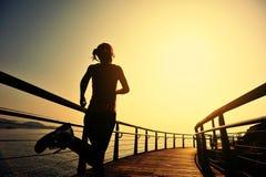 Sportkvinnaspring på trästrandpromenadsoluppgångsjösidan Royaltyfri Fotografi