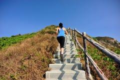 Sportkvinnaspring på bergtrappa Arkivfoton