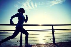 Sportkvinnaspring på trästrandpromenadsoluppgångsjösidan Royaltyfri Bild