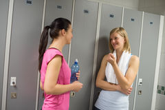 Sportkvinnor som talar i omklädningsrum med låsbara skåp Royaltyfri Bild