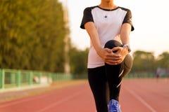 Sportläuferfrau, die für das Aufwärmen vor dem Betrieb von Handelnübungen und von Trainingstraining ausdehnt lizenzfreies stockbild