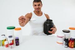Sportler, der über dem weißen Hintergrund hält Vitamine steht stockbilder