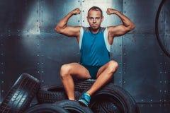 Sportler, der auf der Reifenmaschine sitzt Konzept von CrossFit, von Gesundheit und von Stärke Stockbild