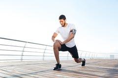 Sportler, der Beine auf Pier aufwärmt und ausdehnt Lizenzfreies Stockbild