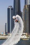 Sportler, der Bremsungen auf einem Hintergrund der Türme Dubai-Jachthafens im Wettbewerb für den Fliegeneinstieg bei SkyDiveDubai Stockbilder