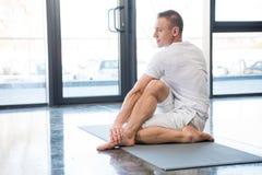 Sportler in der halben spinalen Torsionshaltung, die auf Yogamatte sitzt stockfotografie