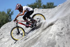 Sportler in der Sportkleidung auf einer Mountainbike fährt auf die Steine Lizenzfreie Stockfotografie