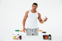 Sportler, der Vitamine und Sportpillen hält lizenzfreie stockbilder