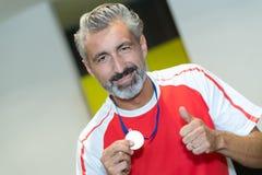 Sportler mit goldener Medaille auf Kasten Lizenzfreie Stockfotografie
