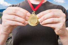 Sportler oder Sieger zeigt seinen Preis - goldene Medaille Lizenzfreie Stockbilder
