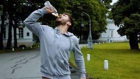 Sportlergetränktrinkwasser vom Flaschenspritzwasser stock video footage