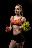 Sportlerin, die Blätter des grünen Pfeffers und des Kopfsalatsalats hält Lizenzfreies Stockfoto