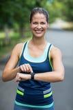 Sportlerin, die ihre Herzfrequenzuhr überprüft Stockbild
