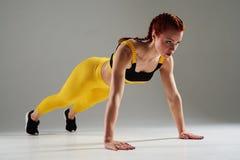 Sportlerin, die Plankenübung tut Stockfotografie