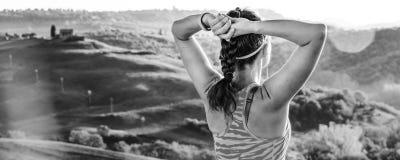 Sportlerin gegen die Landschaft von Toskana untersuchend Abstand Stockfotos