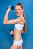 Sportlerintraining mit den Dummköpfen lokalisiert auf Blau im Studio lizenzfreie stockbilder