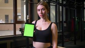 Sportlerinvertretungstablette mit chromakey Grünschirm in die Kamera, die ruhig und in der Turnhalle konzentriert ist, stock video