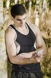 Sportlerläufermann, der seine Statistiken am intelligenten Telefon schaut Stockbild