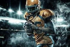 Sportlerspieler des amerikanischen Fußballs auf dem Stadion, das in Aktion läuft stockfotos