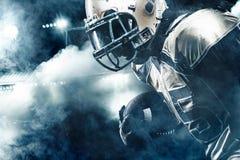 Sportlerspieler des amerikanischen Fußballs auf dem Stadion, das in Aktion läuft lizenzfreie stockfotos