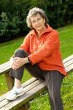 Sportliche ältere Frau auf einer Bank stockfotografie