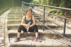 Sportliche asiatische Frau, die draußen stillstehendes Trinkwasser sitzt Stockfotografie