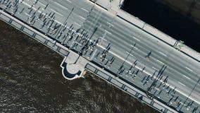 Sportliche Athleten lassen Marathon entlang enormer grauer Flussbrücke laufen stock video