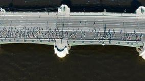 Sportliche Athletenmengen lassen Marathon entlang langer grauer Brücke laufen stock footage