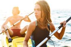Sportliche attraktive Kayak fahrende Paare stockbilder