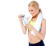 Sportliche blonde Frau, die mit Wasserflasche aufwirft Stockbild