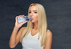 Sportliche blonde Frau trinkt Wasser Stockbild
