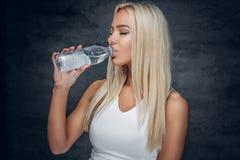 Sportliche blonde Frau trinkt Wasser Stockfoto
