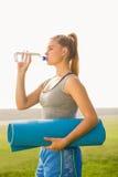 Sportliche blonde haltene Übungsmatte und Trinkwasser Lizenzfreie Stockfotografie