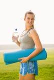Sportliche blonde haltene Übungsmatte und Wasserflasche Stockfotografie