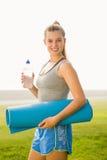 Sportliche blonde haltene Übungsmatte und Wasserflasche Lizenzfreies Stockfoto