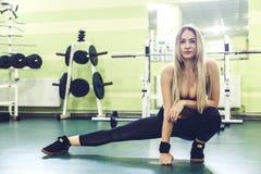 Sportliche blonde junge Frau, die vor der Ausbildung in einer TURNHALLE aufwärmt Lizenzfreie Stockbilder