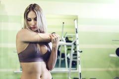 Sportliche blonde junge Frau, die vor der Ausbildung in einer TURNHALLE aufwärmt Stockfotos