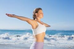 Sportliche blonde Stellung auf dem Strand mit den Armen heraus Lizenzfreie Stockfotos