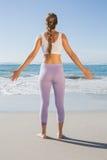 Sportliche blonde Stellung auf dem Strand mit den Armen heraus Stockfotos